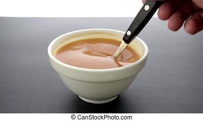 Bowl of tomato soup being stirred.