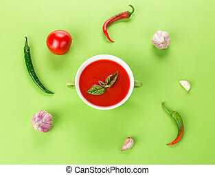 Bowl of tomato soup on a green background.