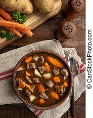 Bowl of vegetable beef soup with carrots and potatoes on a rustic wooden table.  Overhead view
