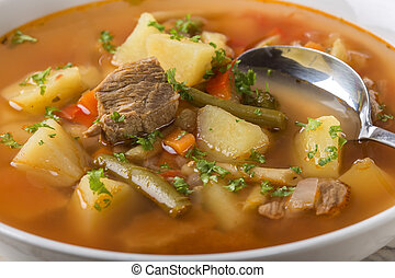 Bowl of vegetable beef soup with spoon - Close up of bowl of...