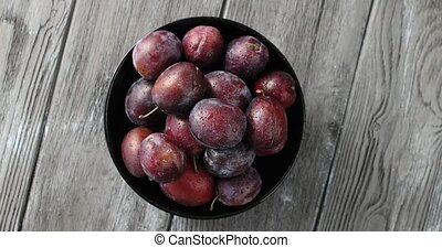 Bowl of wet ripe plums - Top view of round bowl filled with...
