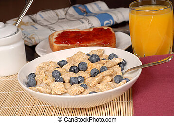 Bowl of wheat cereal with blueberries, toast, orange juice and newspaper