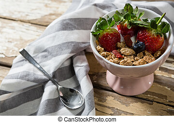 Bowl of wheat flakes with strawberries and blueberry