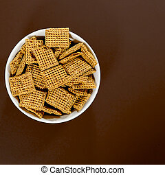 Bowl of Wholegrain Shreddies Breakfast Cereals Against a Brown Background With No People