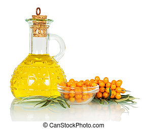Bowl sea buckthorn berries and oil bottle isolated on white.