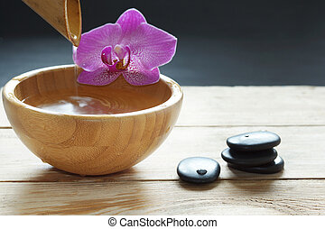 Bowl, which pours transparent water from the bamboo, orchid flowers and stones for a hot massage on a wooden table
