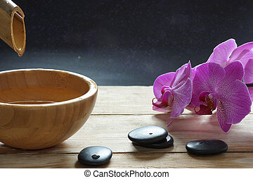 Bowl, which pours transparent water from the bamboo stem, orchid flowers and stones for a hot massage on a wooden table