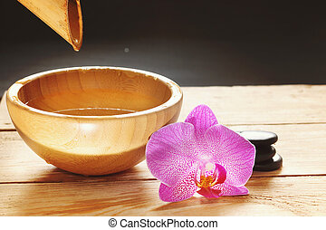 Bowl, which pours water from the bamboo stem, orchid flowers and stones for a hot massage on a wooden table