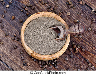 Bowl with black pepper on wooden background