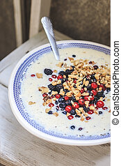 bowl with blue national pattern with cottage cheese and yogurt smoothie with chia, raspberries, red currants, blueberries, blackberries, walnuts on a white wooden table. Top view, close up.
