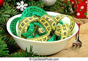 Bowl with centimeter and christmas decoration on table