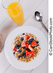 bowl with cereal musli and orange juice on the white table