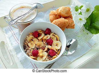 Bowl with cereals with fruits and berries and cup of coffee with croissants