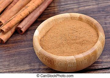 Bowl with cinnamon on table