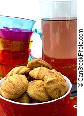 Bowl with cookies, stack of glasses and carafe with lemonade