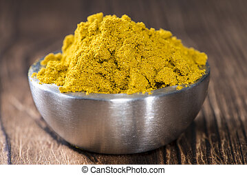 Bowl with Curry Powder on dark wooden background