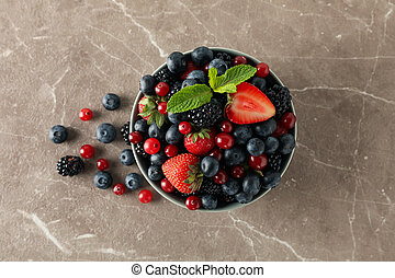 Bowl with fresh berries on gray table, top view