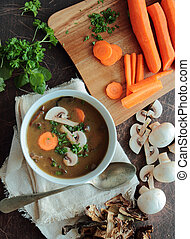 Bowl with fresh mushroom soup with parsley and carrot