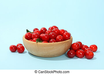 Bowl with fresh red cherry on blue background, close up