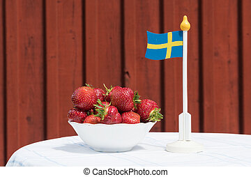 Bowl with fresh strawberries and a swedish flag
