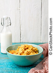 Bowl with oat flakes on a blue wooden table.