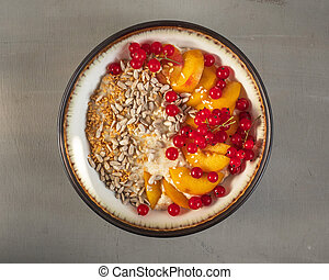Bowl with oatmeal and fresh fruit and berries, top view