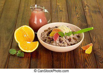 Bowl with oatmeal, pitcher juice, fruits on background dark wood.
