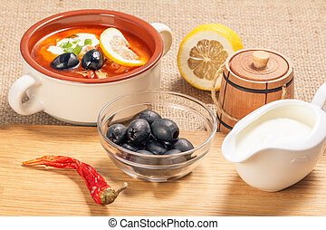 Bowl with olives, dried red pepper on cutting board and ceramic soup bowl with saltwort, sauceboat and cut lemon.