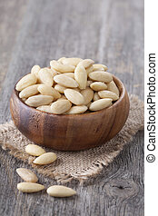 Bowl with peeled almonds nuts on wooden table