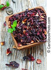 Bowl with petals of hibiscus tea.
