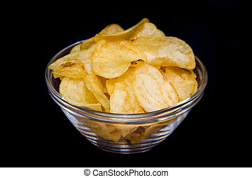 Bowl with potato chips on a black background