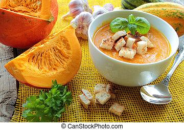 Bowl with pumpkin soup and fresh pumpkins vegetables