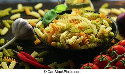 Bowl with raw macaroni of different color - From above view...