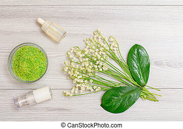 Bowl with sea salt, bottles with cream for face skin and aromatic oil, green leaves and bouquet of lilies of the valley.