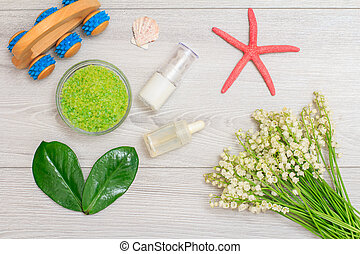 Bowl with sea salt, green leaves, bottles with cream for face skin and aromatic oil and bouquet of lilies of the valley