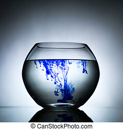 spherical bowl filled with a transparent solution which is blending with a blue dye against a gradient grey background and laying on a reflective surface