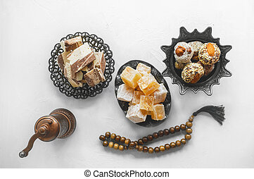 bowl with various pieces of Turkish delight locum and black tea with mint on a light background. Oriental sweets. Top view.