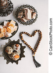 bowl with various pieces of Turkish delight locum and black tea with mint on a light background. Oriental sweets. copy space. Top view.
