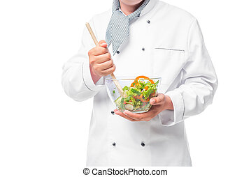 bowl with vegetable salad and a wooden spoon to stir in the hands of chef isolated