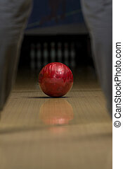 Close-Up Of A Foot Next To A Bowling Ball On A Bowling Lane