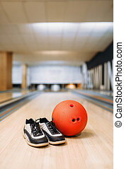Bowling ball and house shoes on lane in club, pins on ...