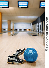 Bowling ball and house shoes on wooden floor in club, pins ...
