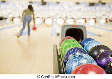 Bowling ball machine with woman bowling in the background