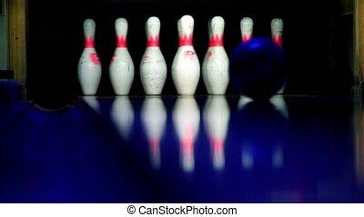 Bowling ball rolls and beats skittles lit in dark, closeup view