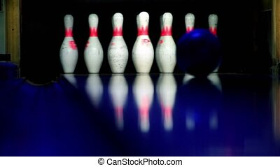 Bowling ball rolls and beats skittles lit in dark, closeup view