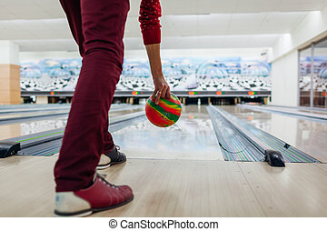 Bowling game. Man having fun playing bowling in club throwing ball on lane. Close up of legs and shoes
