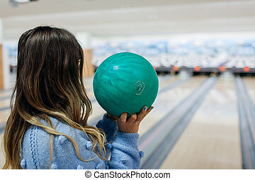 Bowling game. Woman having fun playing bowling in club. Girl holding ball ready to throw it on lane. Lifestyle