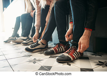 Bowling players ties shoelaces on house shoes - Bowling ...