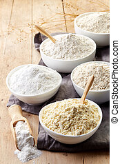 Bowls of various gluten free flour (chick peas, rice, buckwheat, amaranth seeds, almond) on wooden background