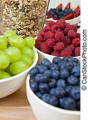 Bowls of healthy breakfast blueberries, raspberries, grapes,...